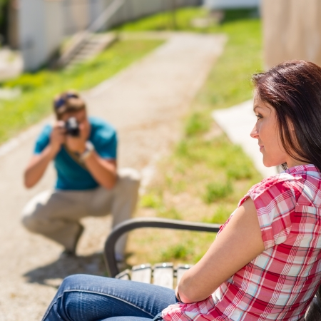 Young man take photo of his girlfriend sitting park bench photo