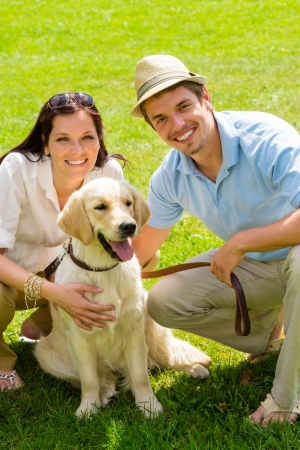 Young happy couple with Labrador dog smiling in park photo