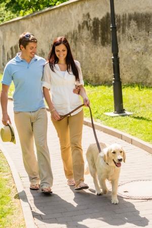 Couple in love walking Labrador dog in park sunny day Zdjęcie Seryjne