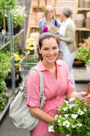 Young woman holding white hibiscus at garden centre shop photo