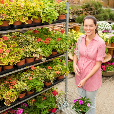 Woman buying potted flower in garden centre with shopping basket photo
