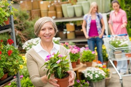 gamme de produit: Achats dame senior pour les fleurs au centre de jardinage sourire Banque d'images