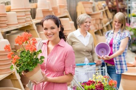 gamme de produit: Jeune femme tenant g�ranium en pot d'argile au centre de jardinage