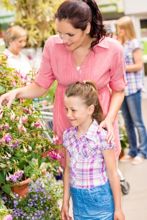 Little girl with her mum shopping at plant market photo