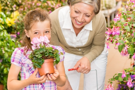 sowbread: Grandmother and granddaughter holding purple potted cyclamen at garden centre