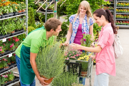 Male garden centre worker selling potted plant to female customers photo