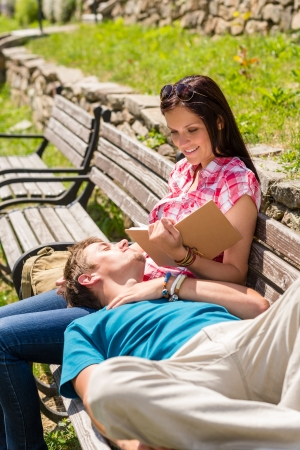 Young happy couple relax on park bench sunny day photo