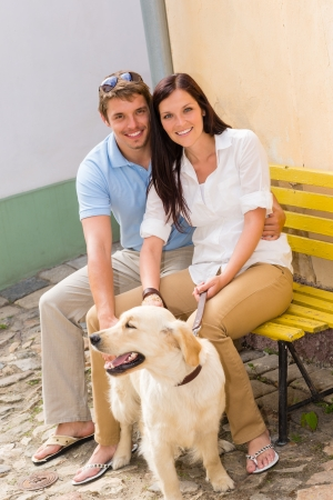 Young smiling couple with dog sitting on yellow bench photo