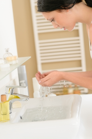 Young woman in bathroom washing her face at wash basin photo