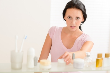 productos de belleza: Mujer joven tener cuidado de la belleza del producto en la estanter�a de ba�o Foto de archivo