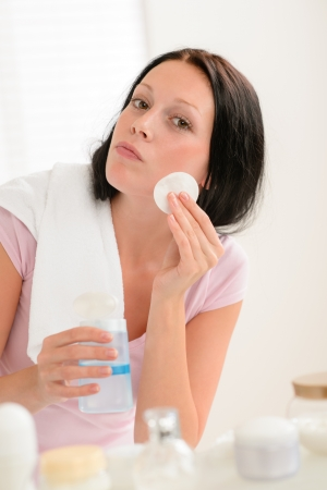 Young brunette woman face tonic cleaning with cotton pad bathroom Stock Photo - 14507230