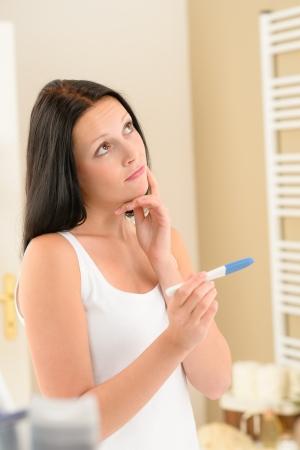impatient: Impatient brunette woman in bathroom waiting for pregnancy test result Stock Photo