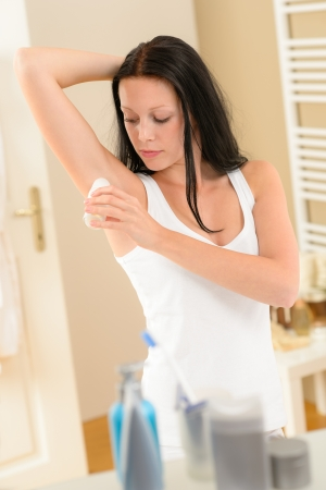 adult armpit: Young brunette woman applying roll-on deodorant under armpit in bathroom