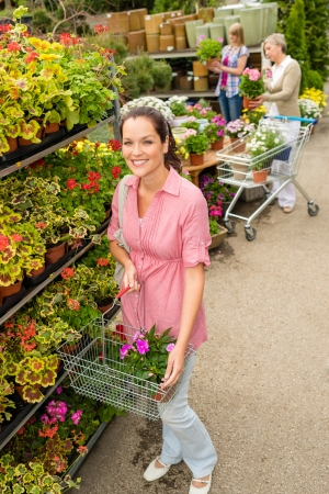 Young woman shopping flowers at market garden centre photo