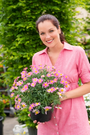 Smiling woman holding pink potted flower in garden center greenhouse photo