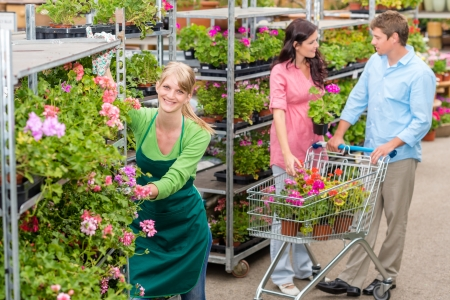 garden center: Garden center worker pushing flower shelves customers shopping