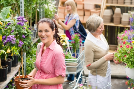 Woman holding potted flower plant in garden shop photo