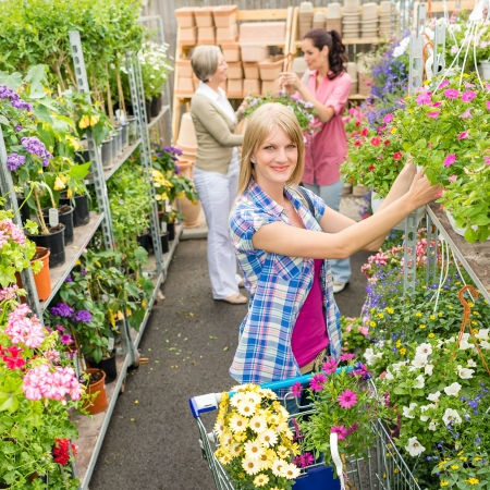 sowbread: Woman shopping for flowers in garden centre  variation of plants