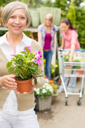 Senior lady shopping for flowers at garden centre smiling Stock Photo - 14547960