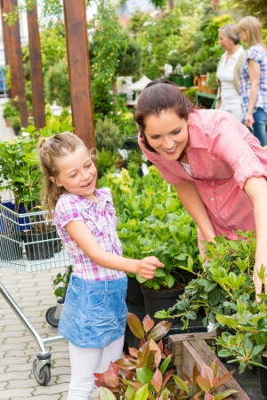 Mother and daughter choosing flowers at garden centre shop Stock Photo - 14547950