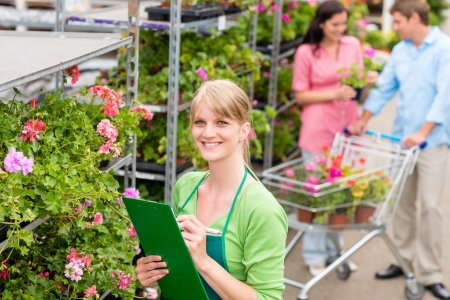 Female florist working at garden centre retail inventory photo