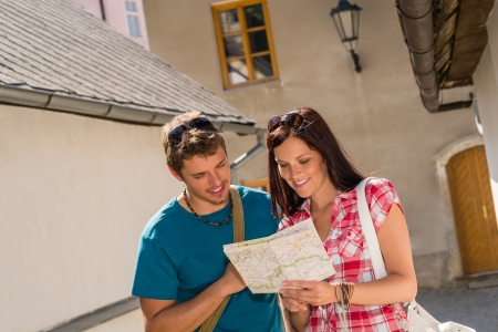 Happy couple looking at map in town travel on holiday photo