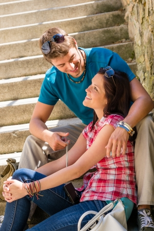 look pleased: Couple smiling at each other on stairs happy looking sitting