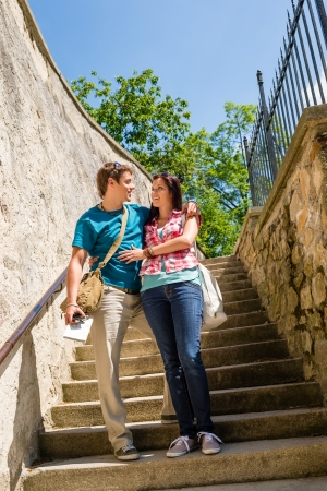 Young couple standing on stairs smiling looking at each other photo