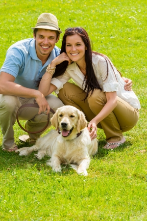 Young happy couple with Labrador dog sitting on grass photo