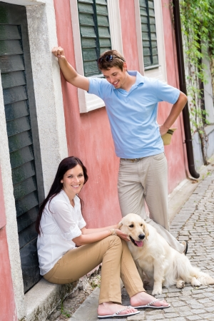 Happy couple resting with dog on street pet smiling love photo