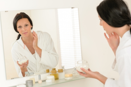 Woman looking in bathroom mirror and applying face moisturizer cream photo
