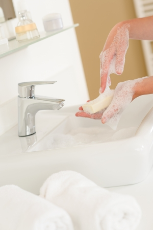 anti bacterial soap: Close-up of washing hands with soap above bathroom sink