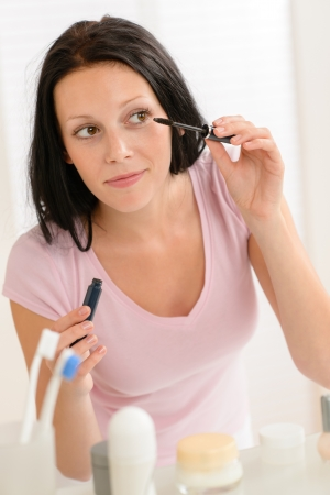 Young woman put mascara in front of bathroom mirror Stock Photo - 14583496