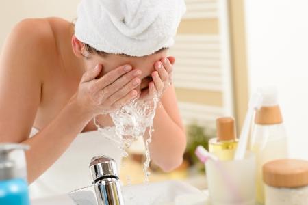visage: Femme �claboussures visage avec de l'eau au dessus du lavabo salle de bain