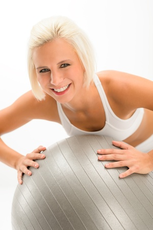 Smiling woman exercising on fitness ball on white background Stock Photo - 14604672