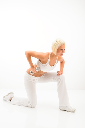 triceps: Young sportive woman strengthen triceps with dumbbells on white background Stock Photo