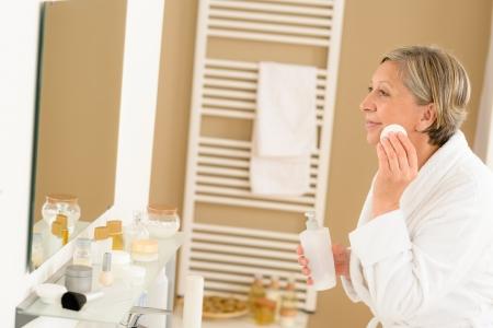 Senior woman in bathroom clean face milk lotion looking mirror photo