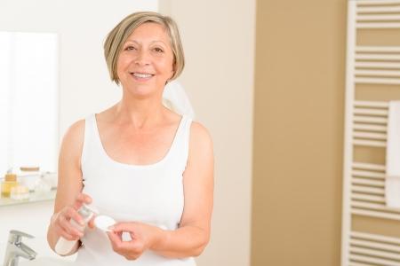 pulizia viso: Senior donna in bagno applicare il make-up viso un batuffolo di cotone rimozione Archivio Fotografico