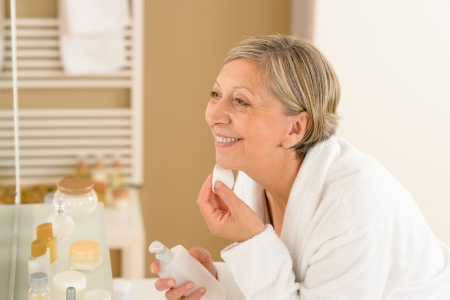 cotton pad: Senior woman in bathroom clean face with lotion and cotton pad Stock Photo