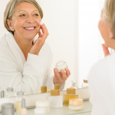 lotions: Smiling senior woman apply anti-wrinkles cream looking in bathroom mirror