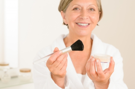 makeup brush: Mature woman hold brush and make-up powder in the bathroom