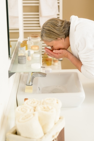 Senior woman in bathroom washing her face at wash basin photo