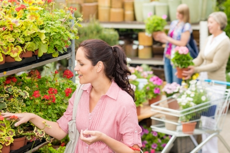 Young woman choosing flowers at garden center green house Stock Photo - 14639907