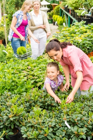 Mother and daughter choosing flowers at garden centre shop Stock Photo - 14639910