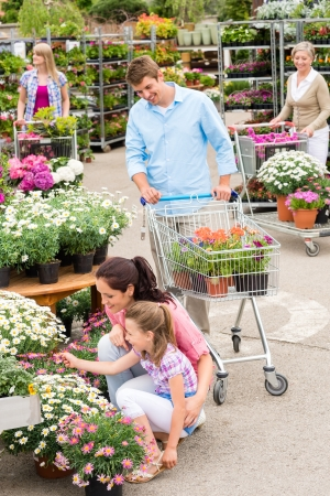 Young family choosing flowers at garden centre retail store photo