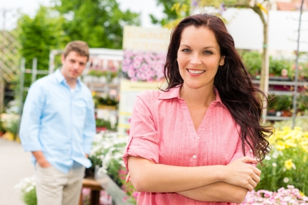 Smiling woman posing at garden centre young man in background photo