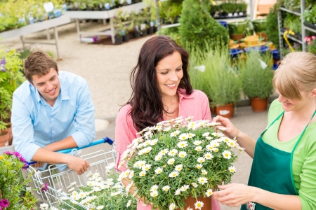 selling service smile: Florist assisting young woman choose flowers at garden shopping center