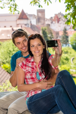 Happy young couple take photo of themselves smiling city tourists photo