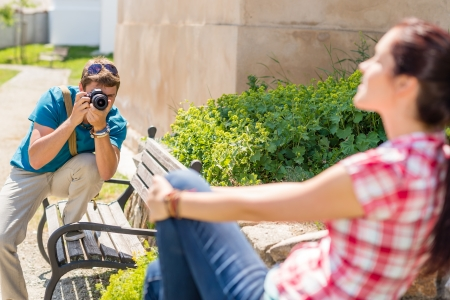 photo shooting: Man taking pictures of woman sitting on bench in park Stock Photo