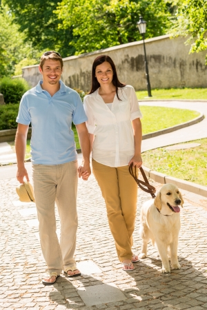 dog leash: Couple in love walking Labrador dog in park sunny day Stock Photo